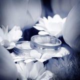 Boucles de mariage avec des fleurs Photographie stock