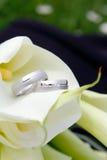 Boucles de mariage avec des fleurs Photo stock