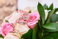 Boucles de mariage avec des roses Photographie stock