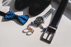 Boucles de mariage Chaussures en cuir noires, montre, noeud papillon bleu et boutons de manchette, sur un filon-couche blanc de f Photo stock