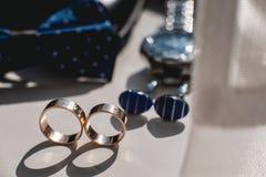 Boucles de mariage Chaussures en cuir noires, montre, noeud papillon bleu et boutons de manchette, sur un filon-couche blanc de f Photo libre de droits
