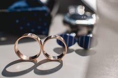 Boucles de mariage Chaussures en cuir noires, montre, noeud papillon bleu et boutons de manchette, sur un filon-couche blanc de f Photographie stock libre de droits