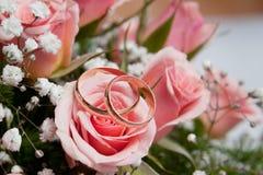 Boucles de mariage d'or sur des couleurs Photo stock