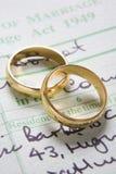Boucles de mariage d'or sur le certificat de mariage image stock