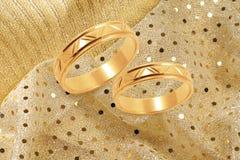 Boucles de mariage d'or sur le fond de fête d'or Image stock