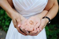 Boucles de mariage dans des mains des nouveaux mariés Photos libres de droits