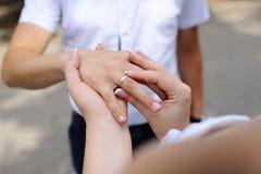 Boucles de mariage dans des mains des nouveaux mariés Photo stock