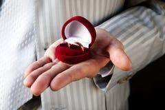 Boucles de mariage dans le cercueil rouge sur la main Photographie stock libre de droits