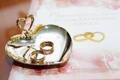 Boucles de mariage et certificat de mariage Photographie stock libre de droits