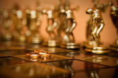 Boucles de mariage et chessmen Photographie stock