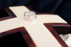 Boucles de mariage et croix en bois Images stock