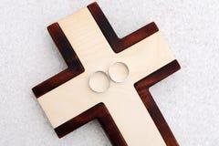 Boucles de mariage et croix en bois Photos stock