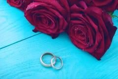 Boucles de mariage et roses rouges Bouquet de mariage sur le fond en bois bleu Foyer sélectif Copiez l'espace et raillez  photographie stock