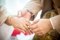 Boucles de mariage Il a mis l'anneau de mariage sur elle Fermez vers le haut du marié Put l'anneau sur la jeune mariée Image libre de droits