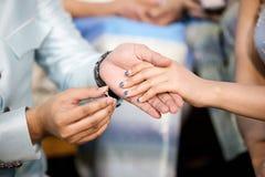 Boucles de mariage Il a mis l'anneau de mariage sur elle Fermez vers le haut du marié Put l'anneau sur la jeune mariée Photographie stock libre de droits