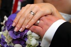 Boucles de mariage sur des mains de mariée et de marié Image libre de droits