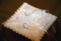 Boucles de mariage sur l'oreiller Photos stock
