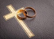 Boucles de mariage sur la bible image stock
