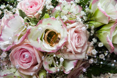 Boucles de mariage sur le bouquet de la mariée Photographie stock libre de droits