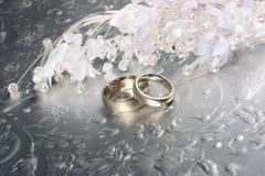 Boucles de mariage sur le fond argenté Photos stock