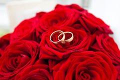 Boucles de mariage sur les roses rouges Photo libre de droits