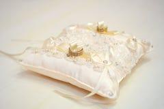 Boucles de mariage sur un coussin photographie stock