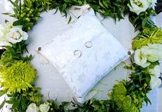Boucles de mariage sur un coussin blanc dans une guirlande des fleurs Photo libre de droits