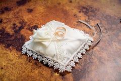 Boucles de mariage sur un oreiller Photo stock