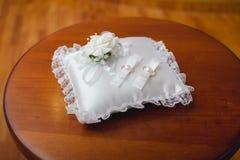 Boucles de mariage sur un oreiller Photos stock