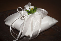 Boucles de mariage sur un oreiller blanc image stock
