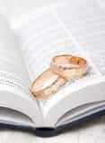 Boucles de mariage sur une bible Photos stock