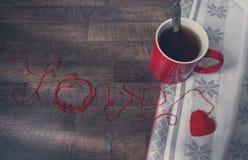 Boucles rouges dans la forme du coeur et de la tasse Photos libres de droits