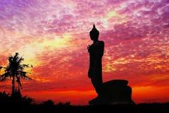 Bouddha se tenant derrière la rive vibrante Sunny Tourism Dawn Sunl de mer de ciel de fond de coucher du soleil de vue urbaine or Photographie stock