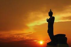 Bouddha se tenant derrière la rive vibrante Sunny Tourism Dawn Sunl de mer de ciel de fond de coucher du soleil de vue urbaine or Images stock