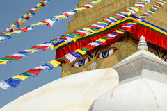 Boudhanath Stupa. Closeup of the Buddha eyes of Boudhanath stupa surrounded by prayer flags in Kathmandu, Nepal. It is the largest stupa in Nepal and the holiest Stock Photos