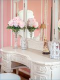 Boudoir table. Bouquet of pink flowers in glass vase on white boudoir table and sweet pink room. Vintage decoration style stock image