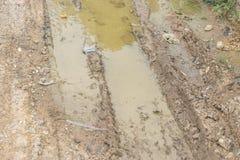 Boue brune humide avec des voies de pneu de bicyclette photo stock