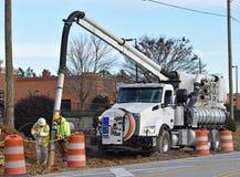 Boue de vide de travailleurs de la construction de tuyau de drainage photos stock