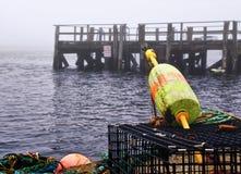 Bouées et trappes de langoustine à un dock Photos stock