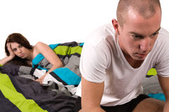 Boufriend feeling troubled about his relation. A young couple in bed with relation problems Stock Photography