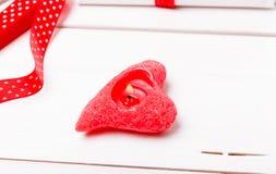 Bougie allumée aux coeurs rouges de forme sur le backround en bois blanc, ruban rouge Concept de Saint Valentin Photographie stock
