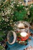 Bougie allumée dans le pot en verre avec les fleurs blanches et les feuilles de vert Photographie stock libre de droits