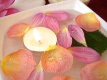 Bougie avec des pétales des fleurs photographie stock libre de droits
