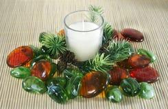 Bougie blanche avec le branchement de pin et les pierres colorées. Photographie stock libre de droits