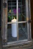 Bougie blanche dans la lanterne décorative avec des fleurs dans le backgroun Photos libres de droits