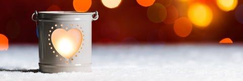 Bougie brûlante dans la neige, avec le bokeh de lumières de Noël Bannière de fête de Web de Noël photos stock