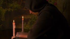 Bougie brûlante dans un petit chandelier blanc Un moine dans un capot lisant un livre Foyer sélectif Evrika obtenu de découverte banque de vidéos