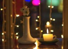 Bougie brûlante et vase blanc avec des fleurs à l'intérieur sur une table dans l'obscurité Photos stock
