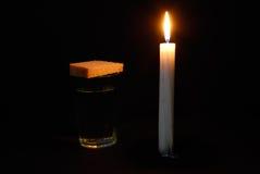 Bougie brûlante, une glace avec de l'eau et pains Photographie stock libre de droits