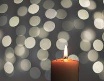 Bougie brûlante avec la lumière de tache floue sur le fond noir Images stock